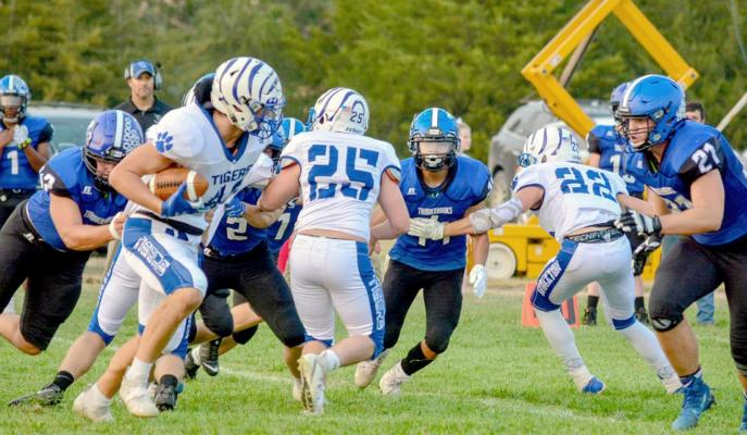 RYLAN BASART, with blockers Justus Hulse (#25) and Deyton Bedore (#22) leading the way, looks for a hole to run through Stockton's game against Wheatland-Grinnell last Friday in Grinnell. The Tigers were defeated 54-22. (Photo courtesy of Brittany Lewis)